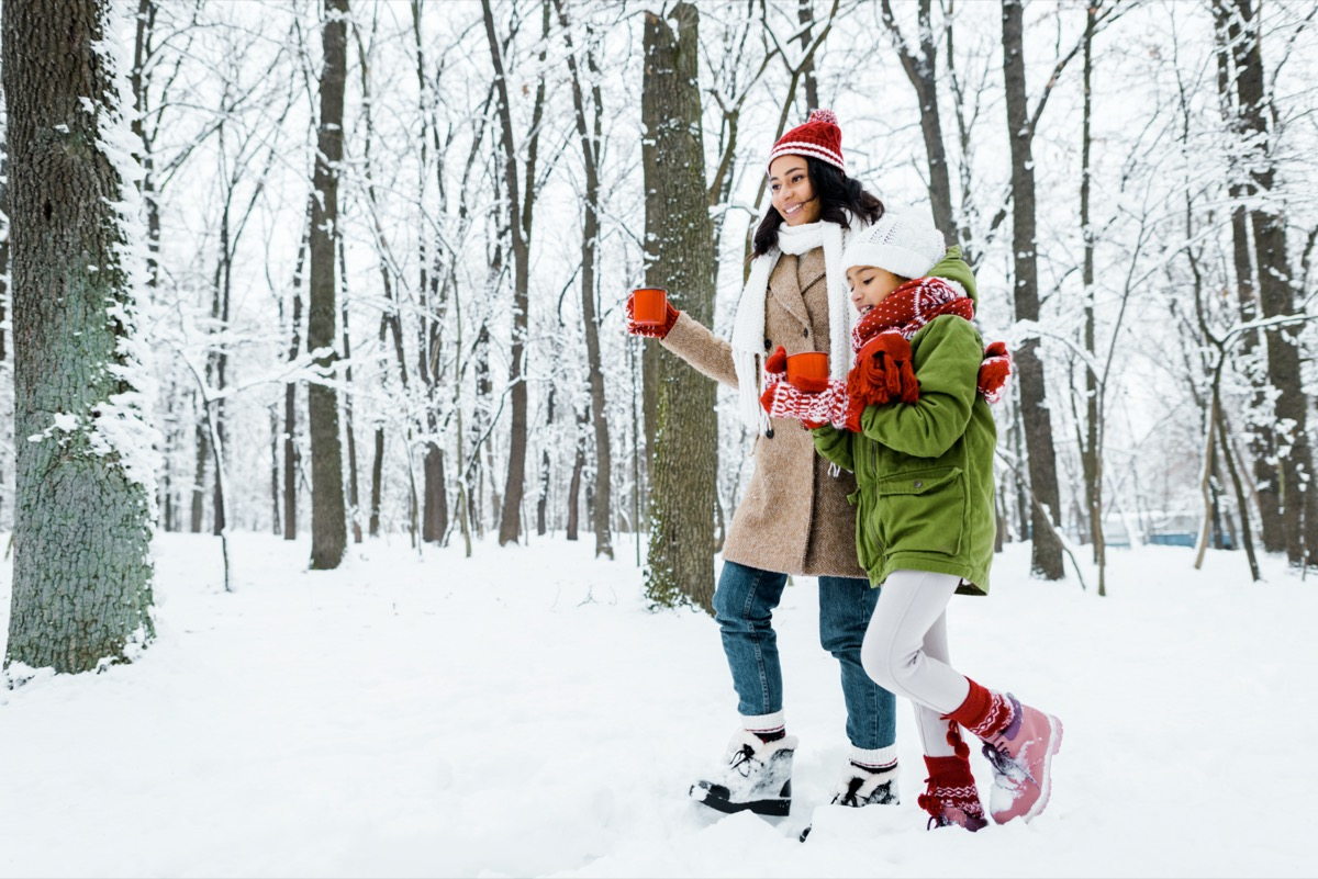 mother and cute daughter walking and holding red cups between trees and looking at snow in snowy forest