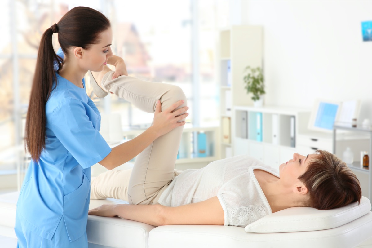 Female orthopedist massaging middle-aged woman in clinic.