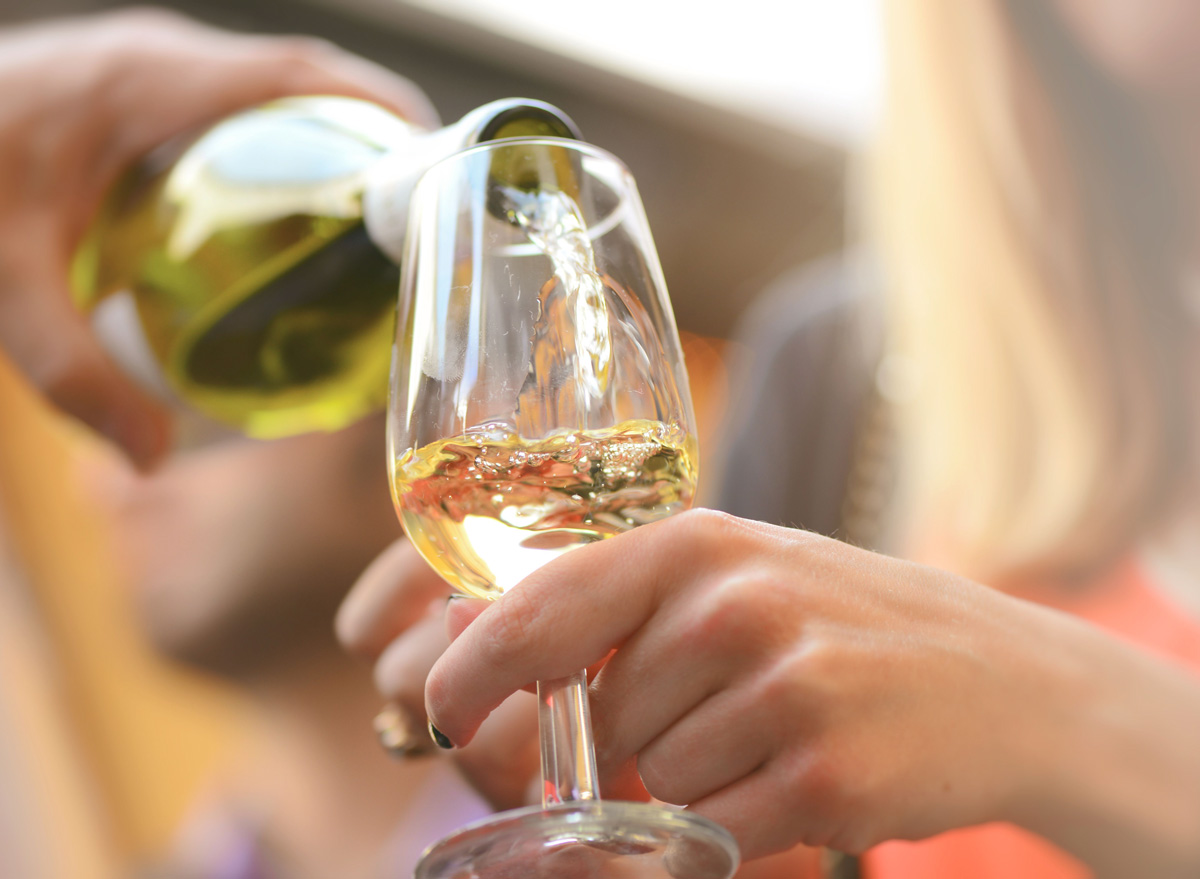 Woman pouring glass of white wine
