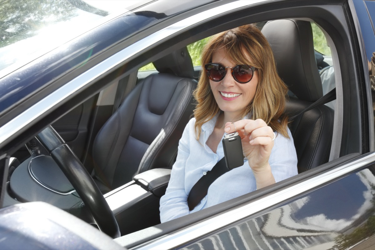 Portrait of smiling driver fastening her seatbelt before driving a car