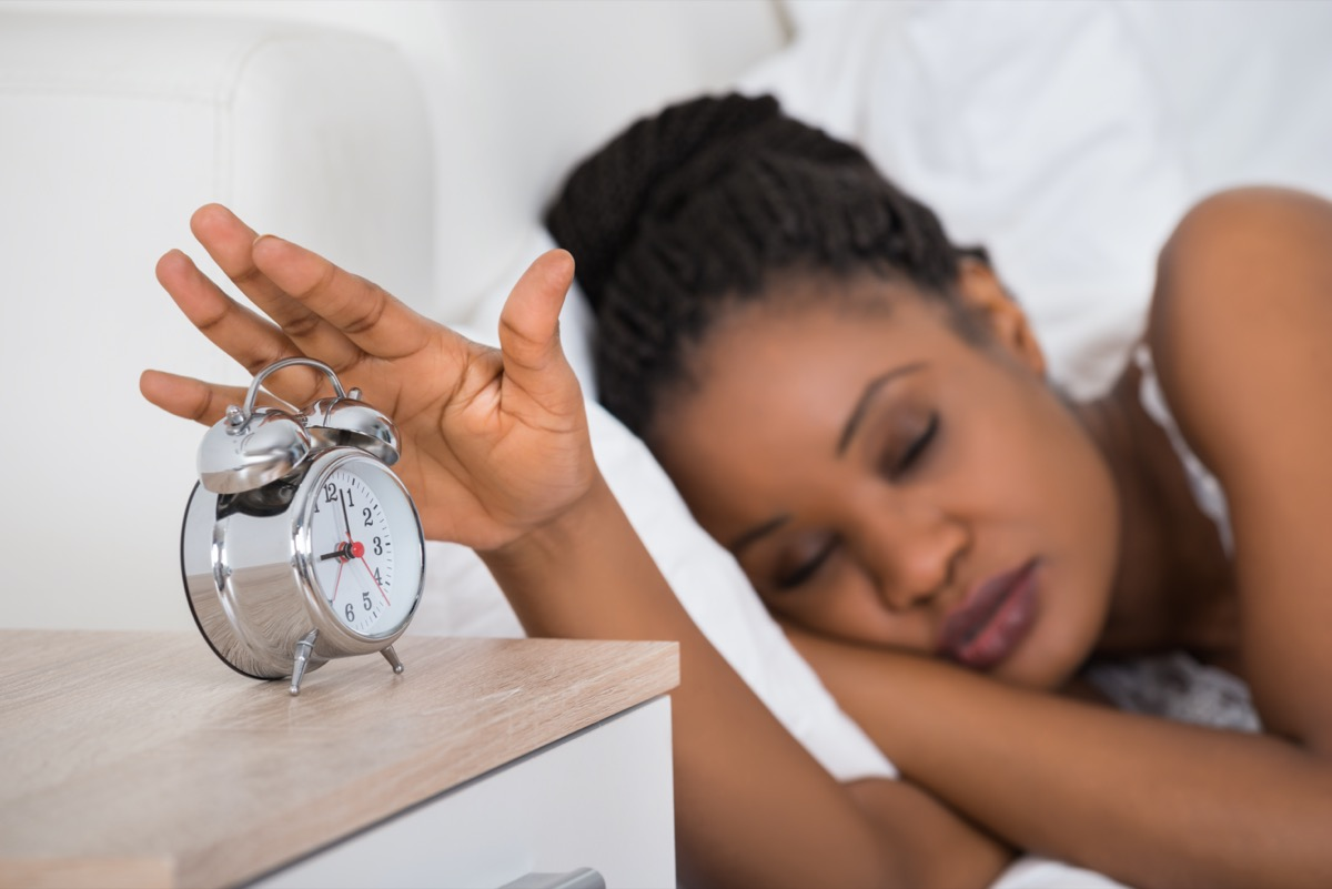 Woman Turning Off Alarm While Sleeping On Bed