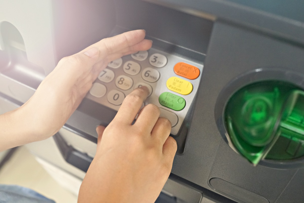 Close up of female hand entering PIN/pass code on ATM/bank machine keypad, she hides it with other hand for security purposes