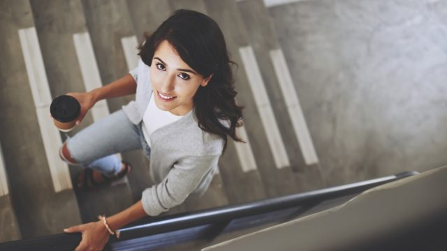 Portrait of lovely brunette walking up the stair, view from above