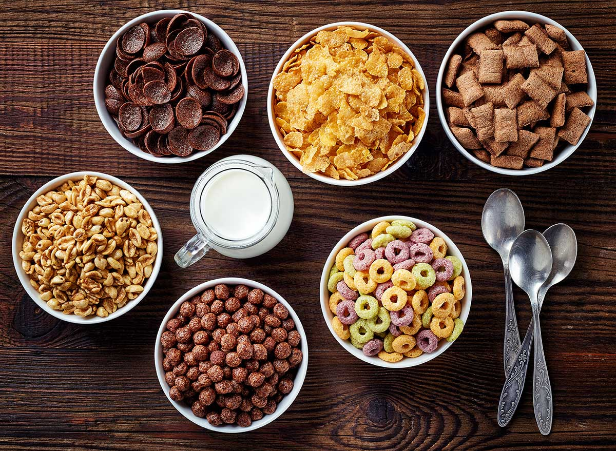 six bowls of different kids' cereals with spoons and glass of milk