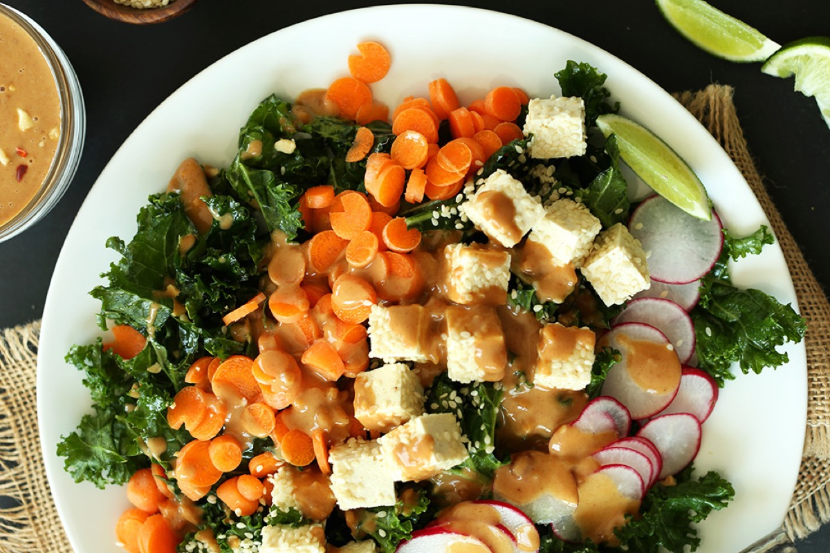 plate of crunchy thai kale salad with carrots tofu and radishes