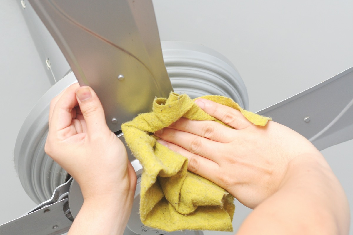 Cleaning the ceiling fan with a cloth.