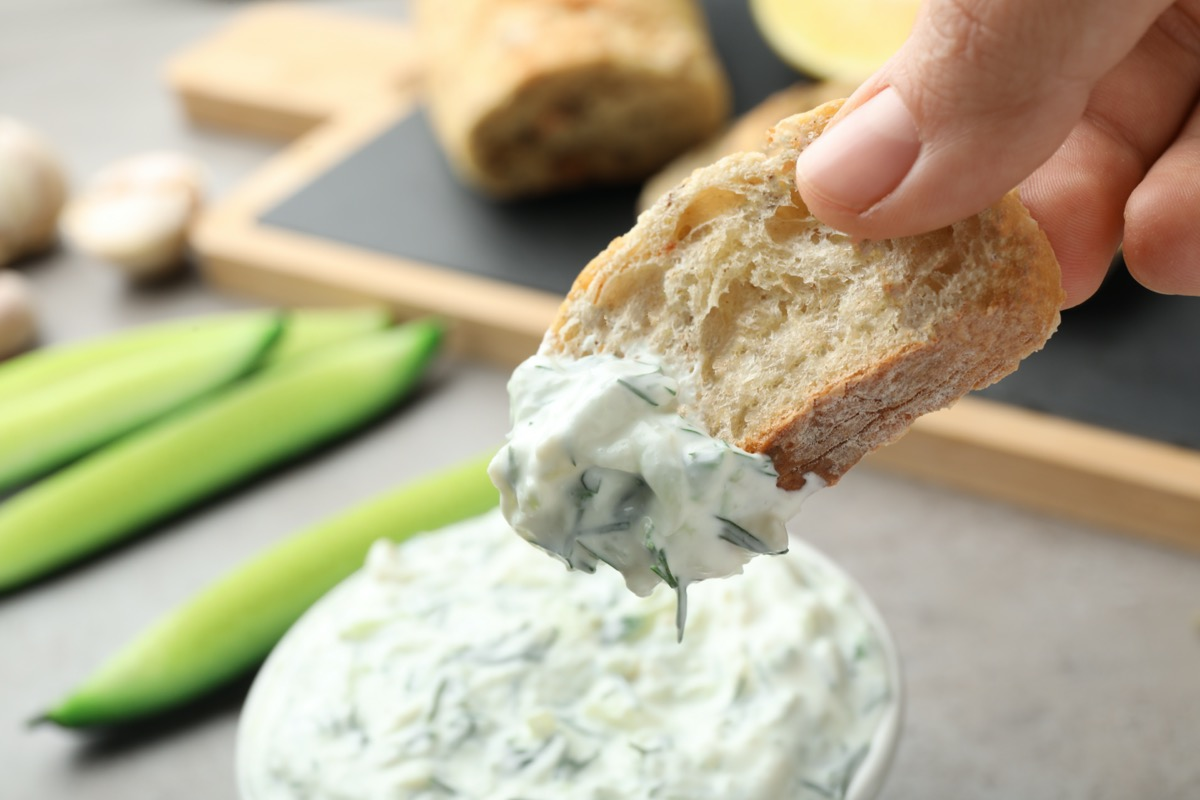 Woman dipping bread in cucumber sauce on blurred background. Traditional Tzatziki