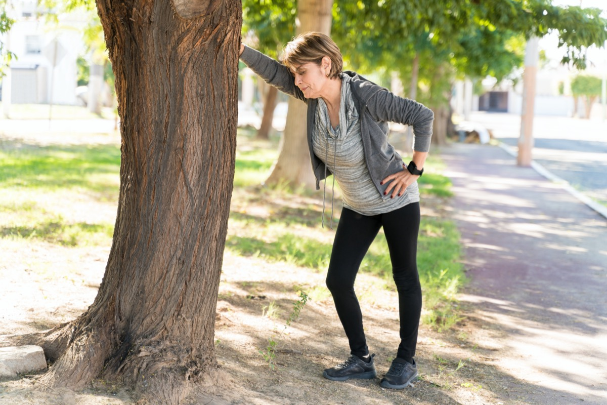 Full length of exhausted senior woman taking a break while leaning on tree in city