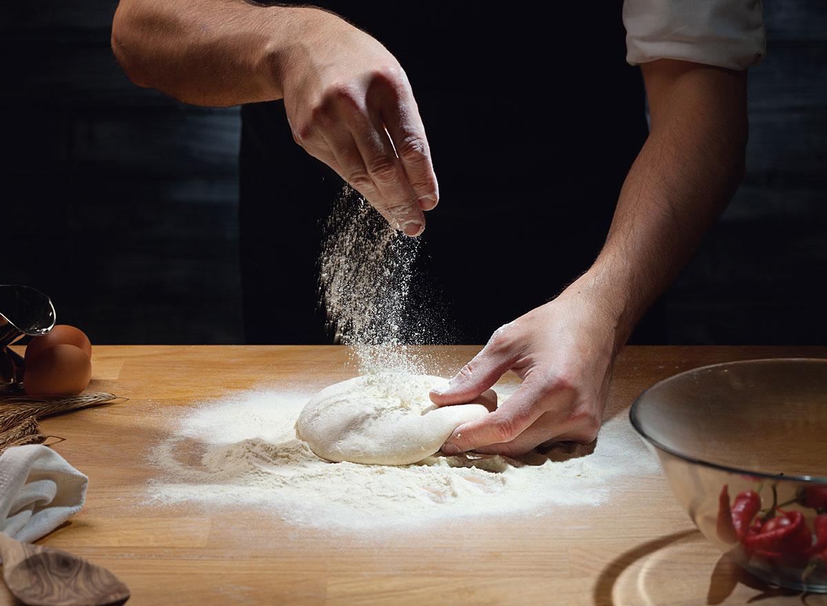 Adding flour on pizza dough