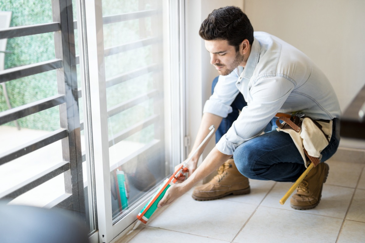 handyman wearing a tool belt and using a sealing gun to seal a glass door frame on a house