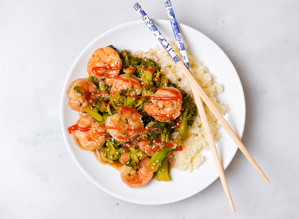 shrimp and broccoli with sriracha on a plate with cauliflower rice