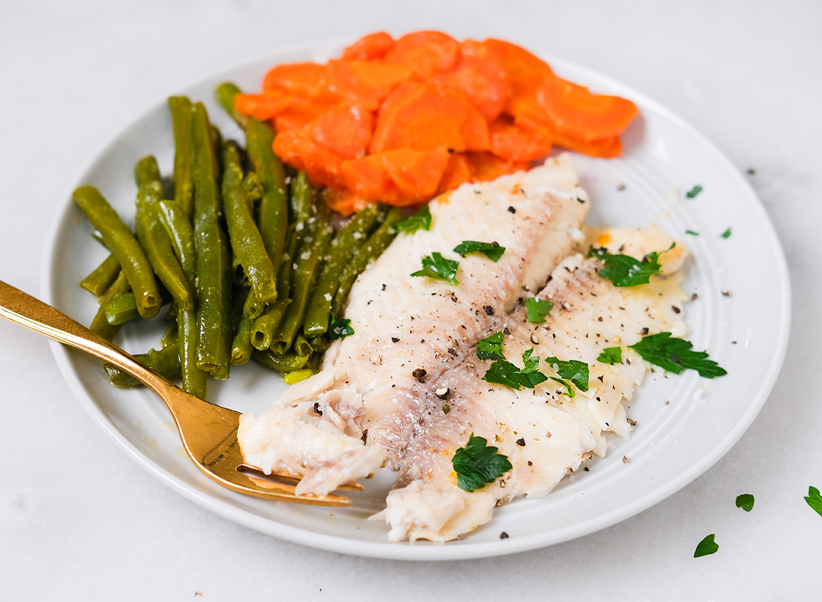 cooked tilapia with vegetables on a plate garnished with parsley