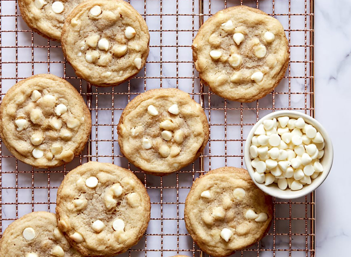 lemon white chocolate cookies on cooling rack with bowl of white chocolate chips