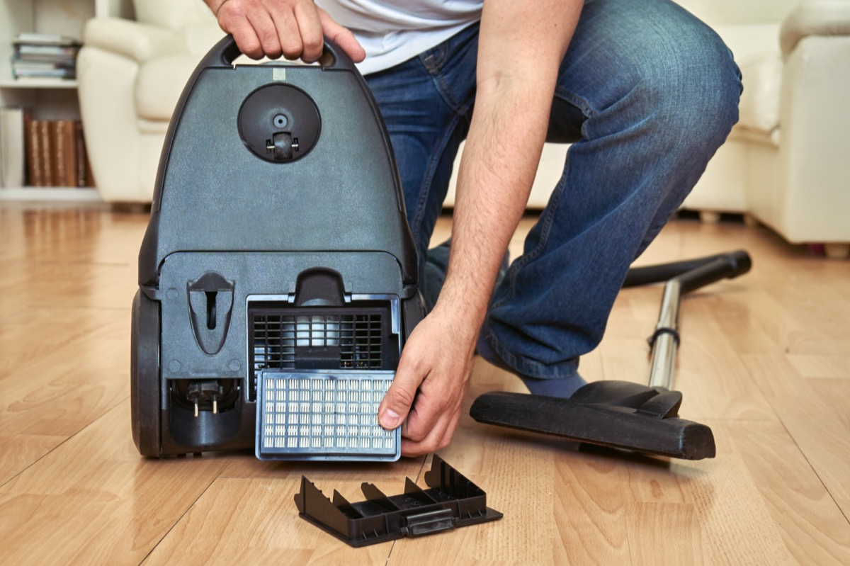 Man replacing an air filter of a vacuum cleaner at home