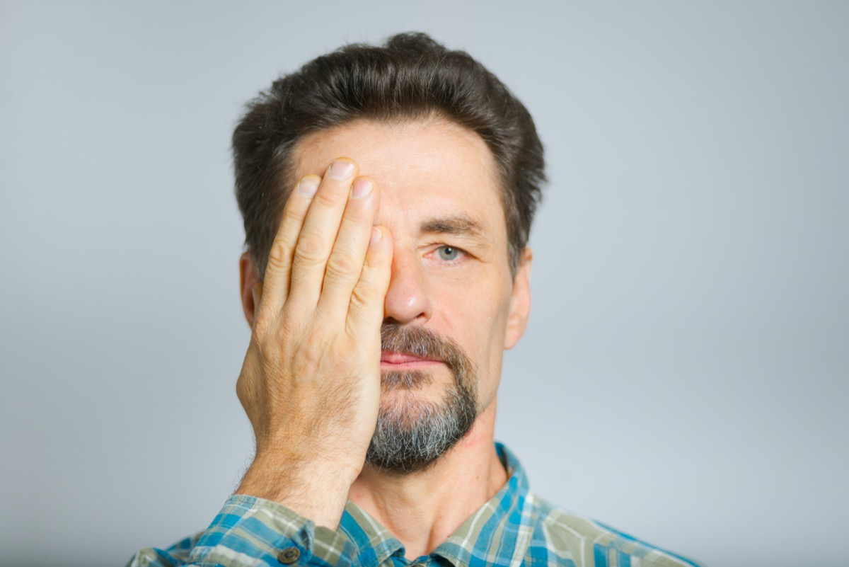 middle-aged man covers eyes with hands, does not see,