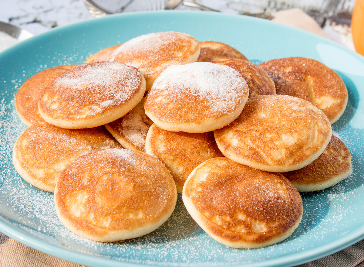 mini pancakes on plate with powdered sugar
