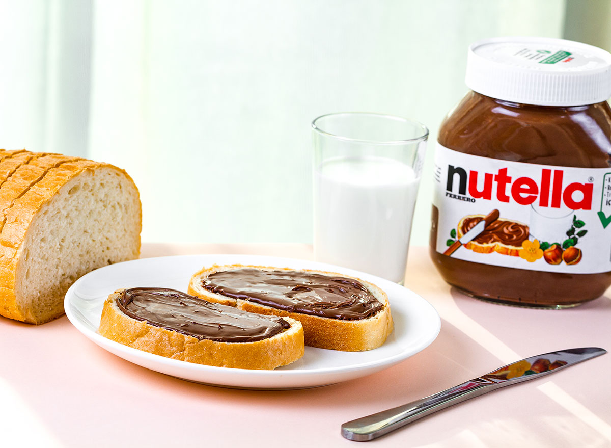 nutella on bread with glass of milk and knife