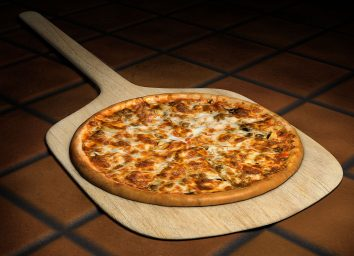 Pizza on wooden pizza peel