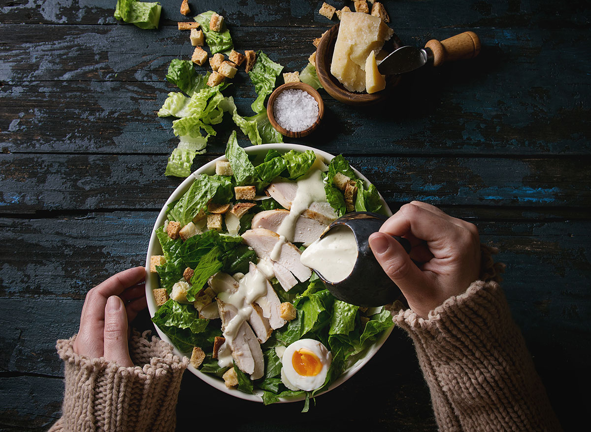 Women pouring dressing on salad