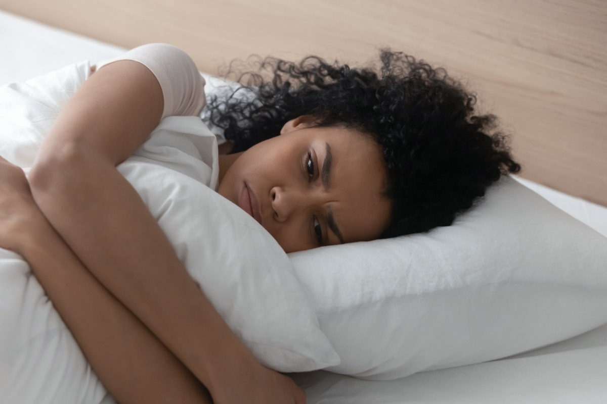 woman hugging pillow lying in bed alone