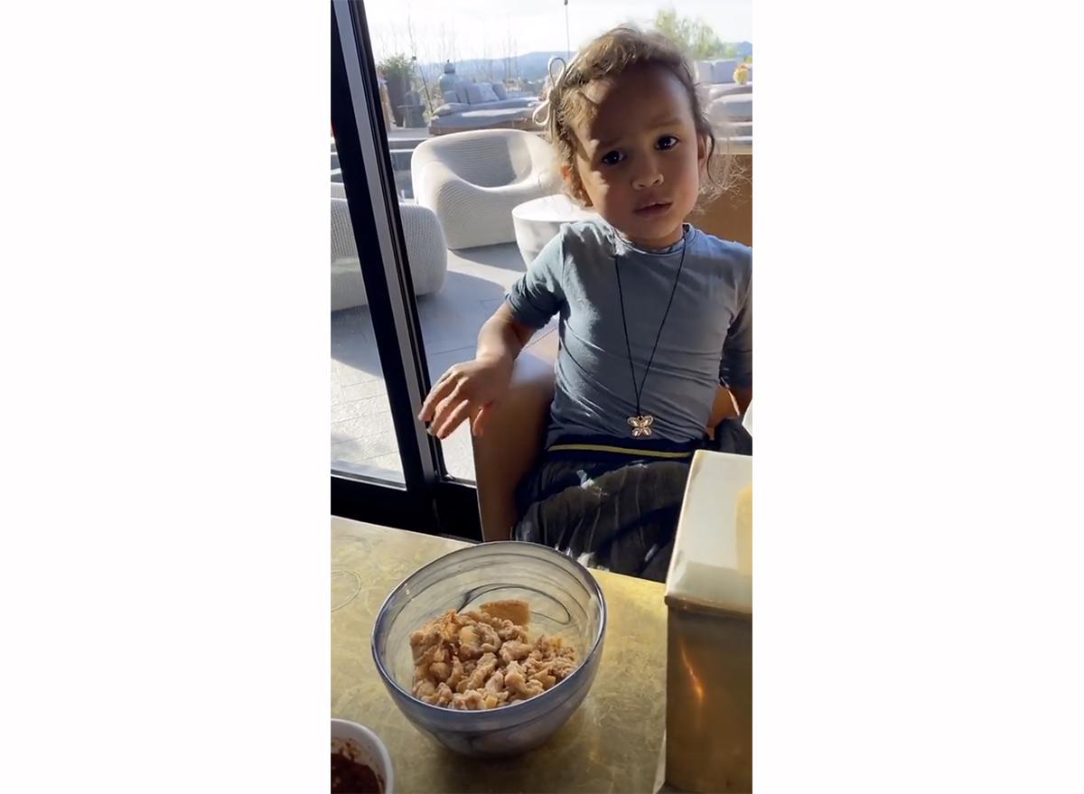 screenshot from chrissy teigen's instagram story of luna eating pork rinds