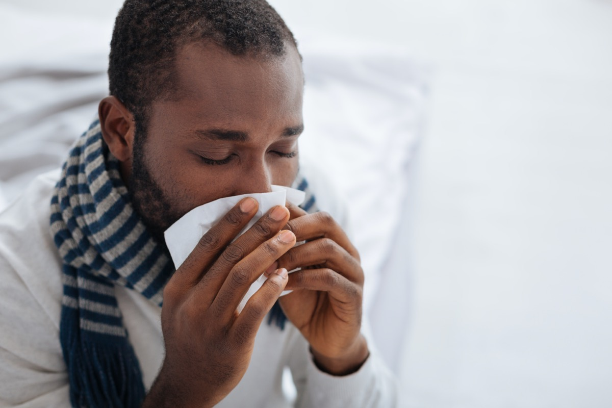 Ill person blowing his nose with closed eyes