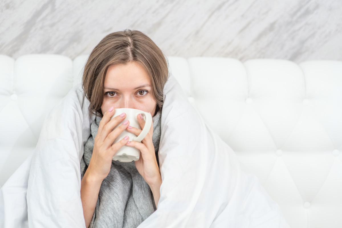 sick woman sitting on the bed wrapped in a white blanket and drink hot tea.