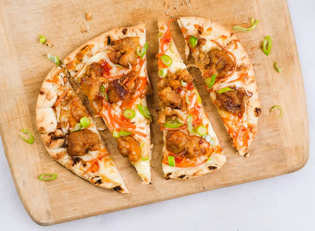 orange chicken flatbread on a cutting board