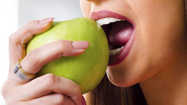 woman biting into apple with teeth