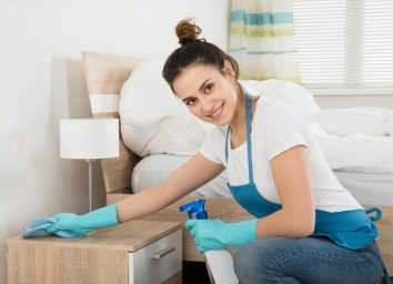 Woman Cleaning Nightstand In Room