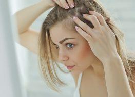 nervous girl looking in the mirror her scalp