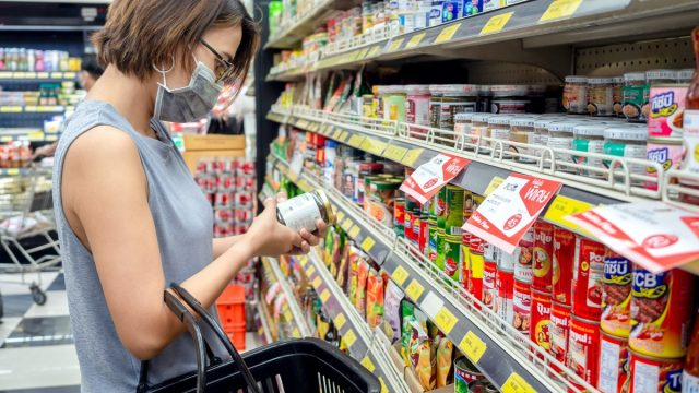 woman wearing protective face mask holding shopping basket and choosing food can product