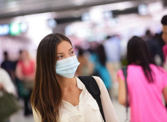 Person wearing protective mask against transmissible infectious diseases and as protection against pollution and the flu