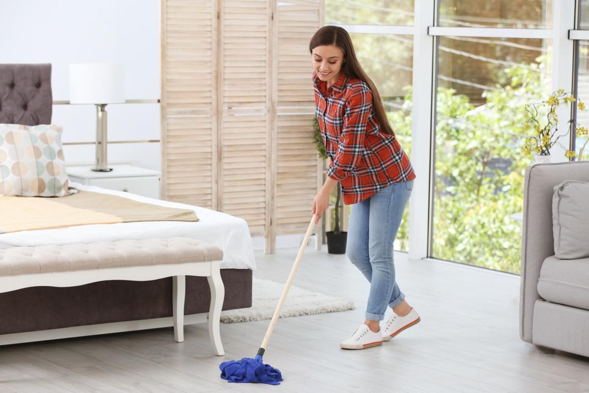 woman cleaning floor with mop in bedroom