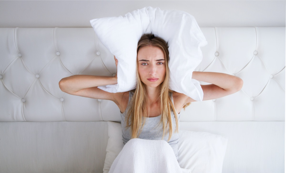 Woman With Insomnia Covering Head And Ears With Pillow