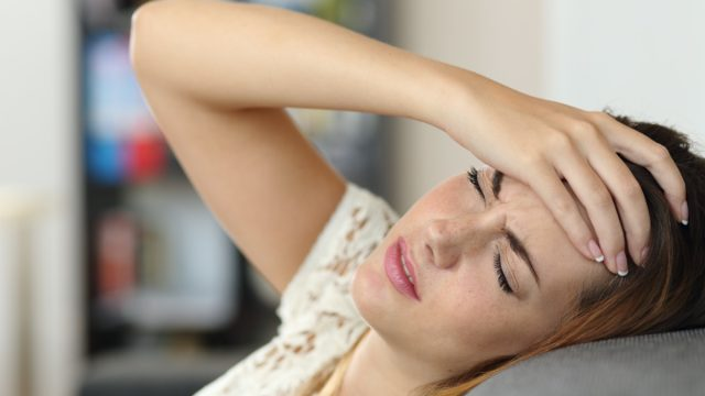 woman in a couch with headache and a hand on forehead
