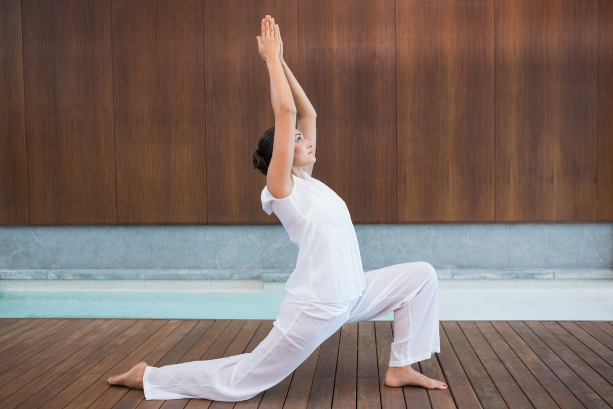 Content brunette in white doing tai chi in health spa