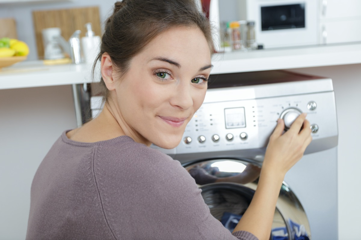 portrait of woman setting dial on her washing machine