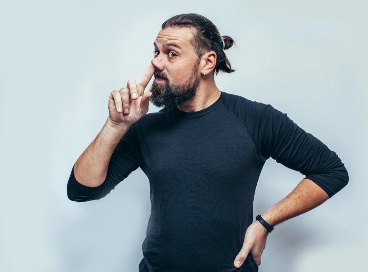 man is emotionally picking his nose