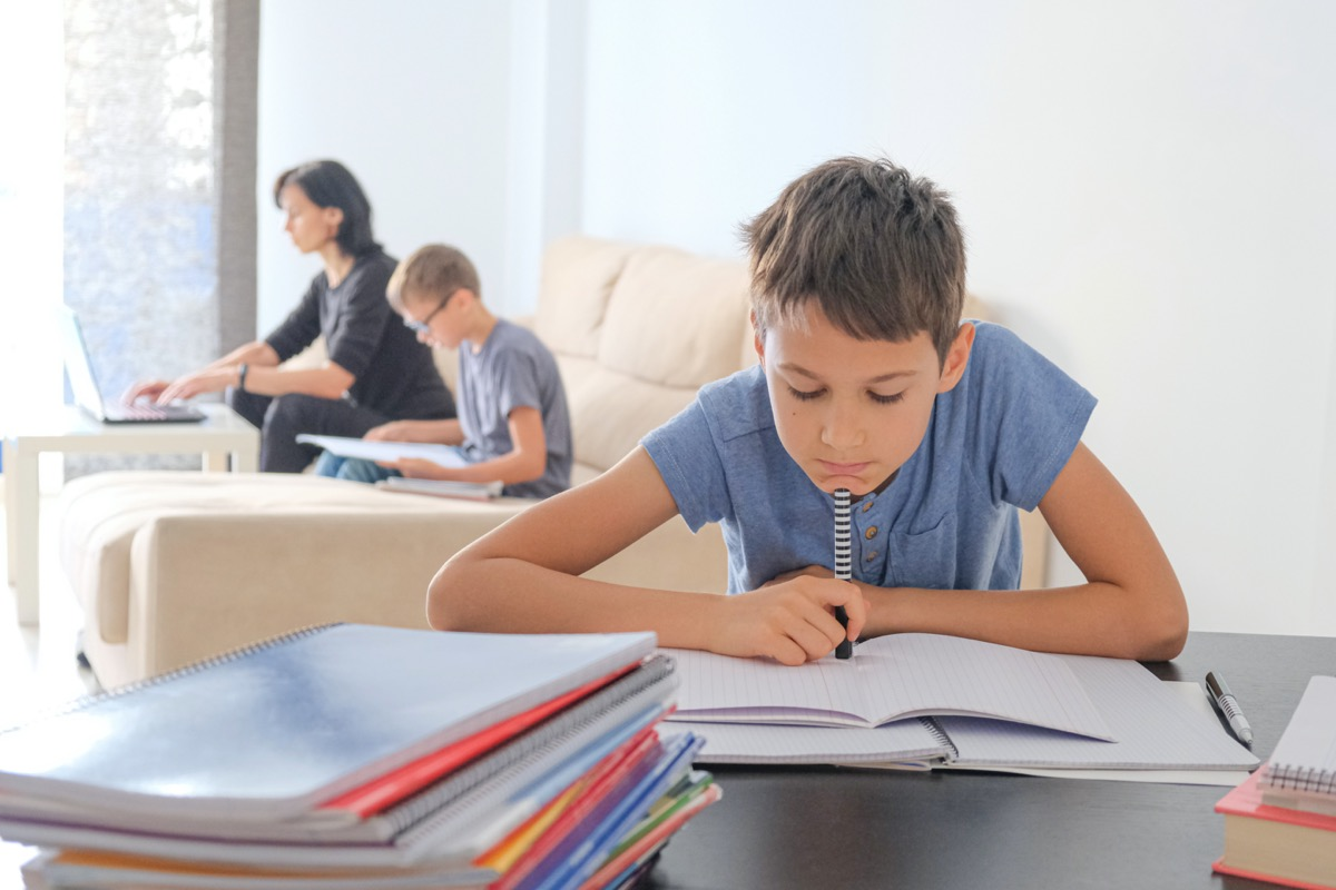 Learning at home, online learning, self quarantine concept. Family at home. Children doing homework and mother working online