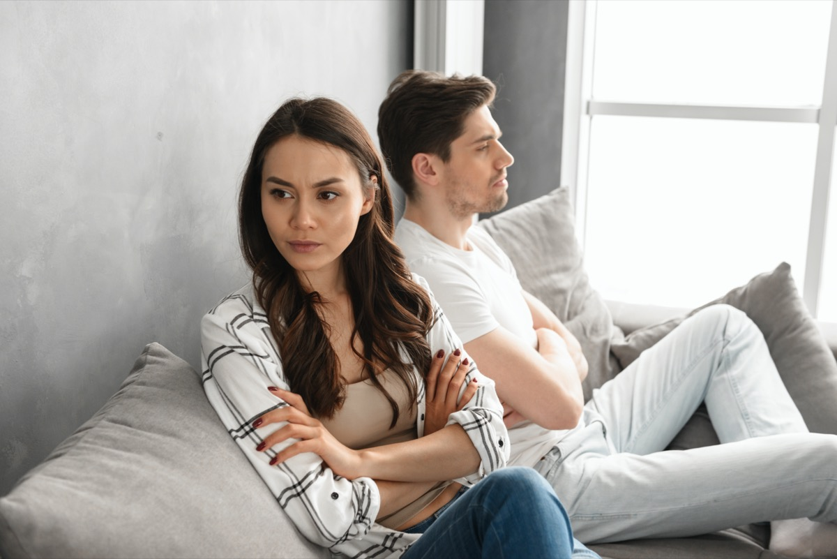 resentful guy and girl acting like arguing couple and not speaking to each other, while sitting together on couch at home