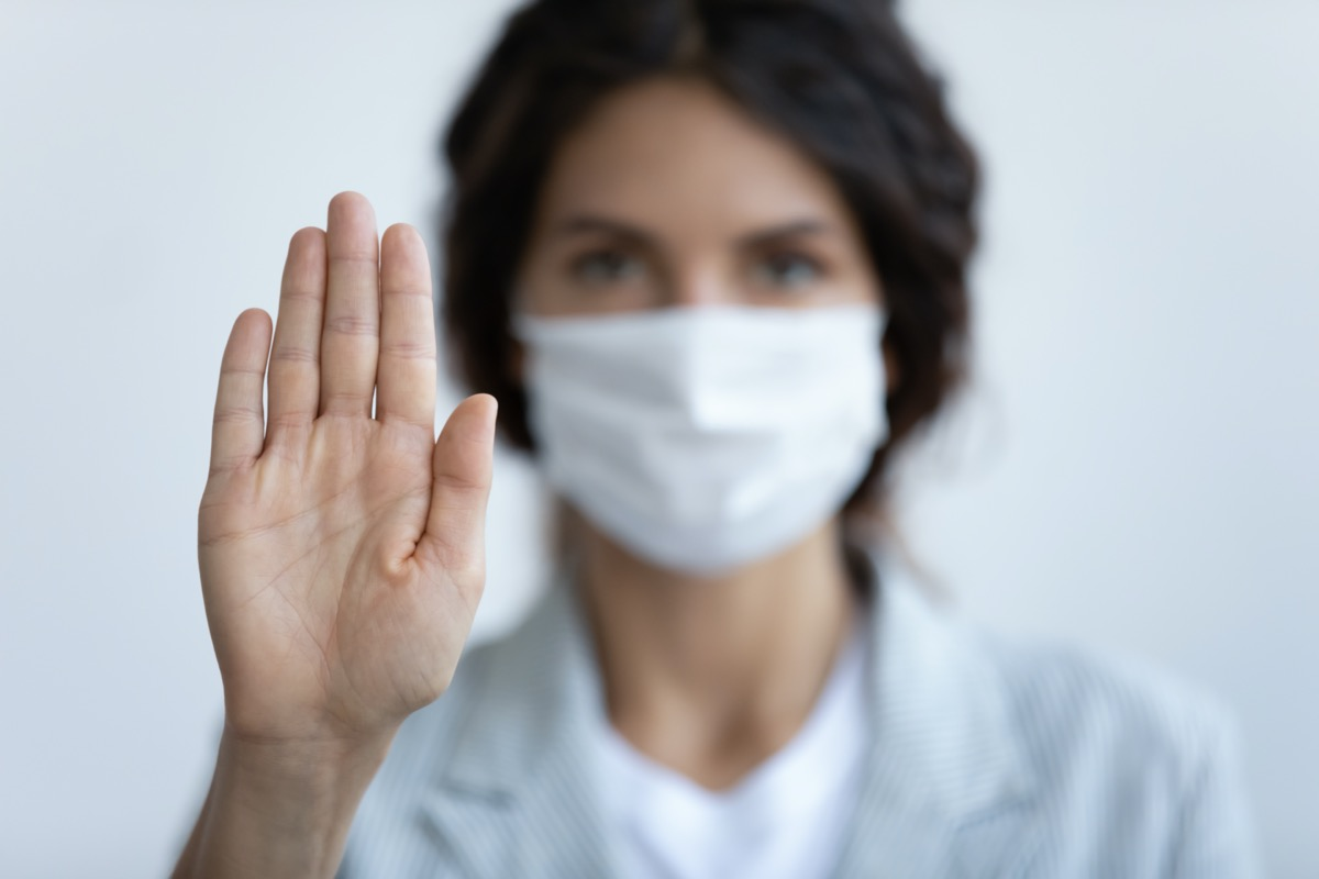 woman in mask focus on stretched hand as symbol of keep distance avoid communication