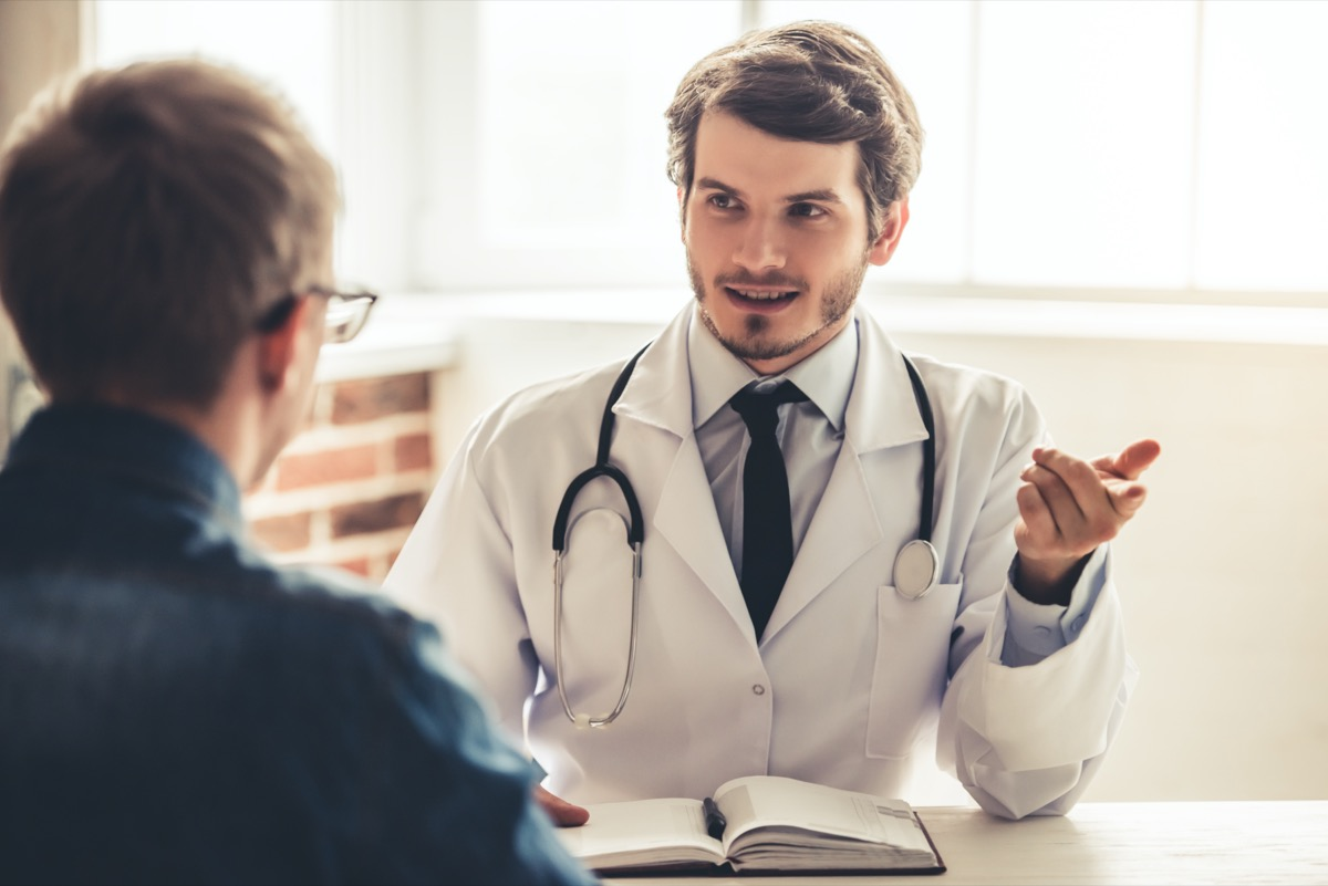 Handsome young doctor in white coat is talking to his patient while working in office