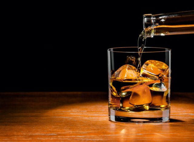 Pouring whiskey drink into glass