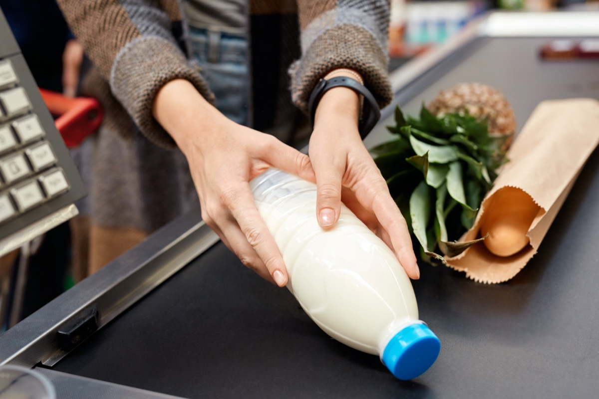 woman at the supermarket doing daily shoppings standing at cashier checkout counter putting milk on conveyor belt