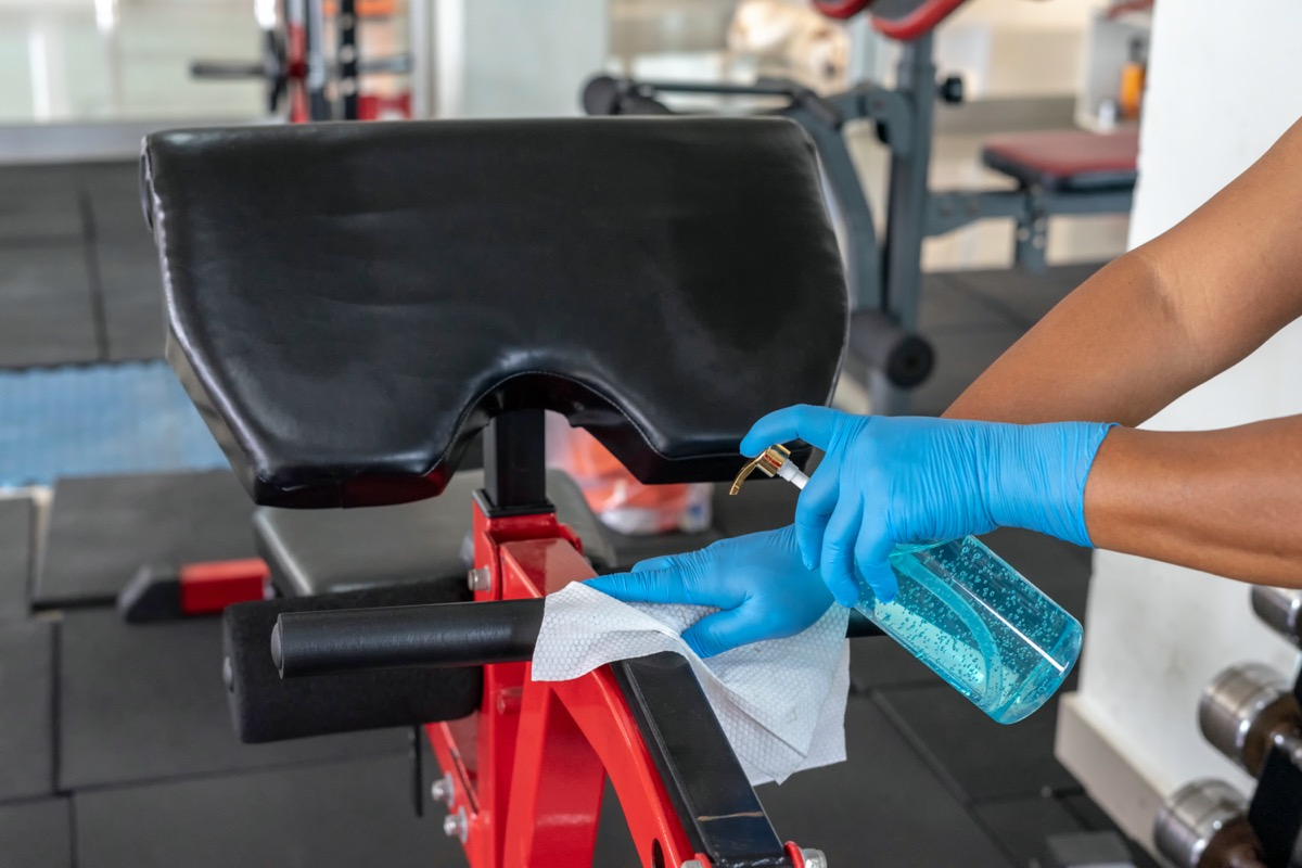 Staff using wet wipe and disinfectant from the bottle spraying sit up bench in gym. Antiseptic,disinfection