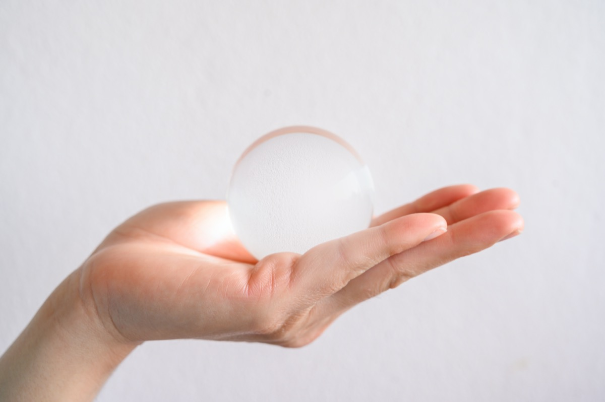 hand holding a clear transparent Crystal ball