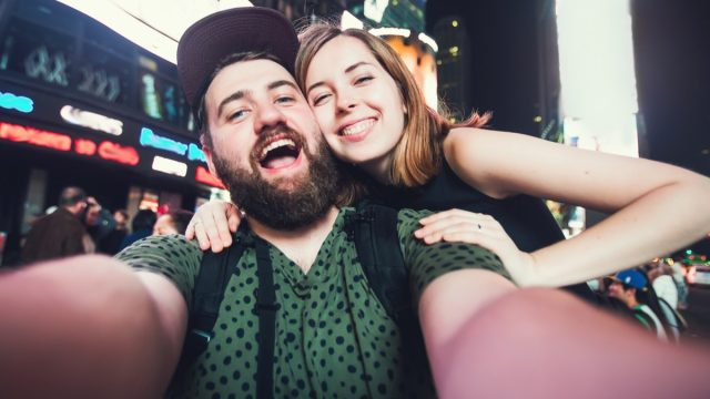Happy dating couple in love taking selfie photo on Times Square in New York while travel across USA on honeymoon