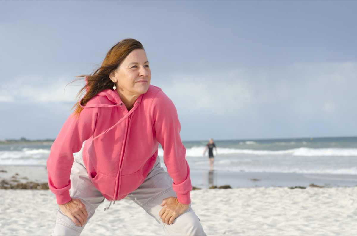 Portrait of confident, healthy and sporty fit attractive looking mature woman in pink sweater, at beach, with isolated storm clouds and wild ocean as background and copy space.