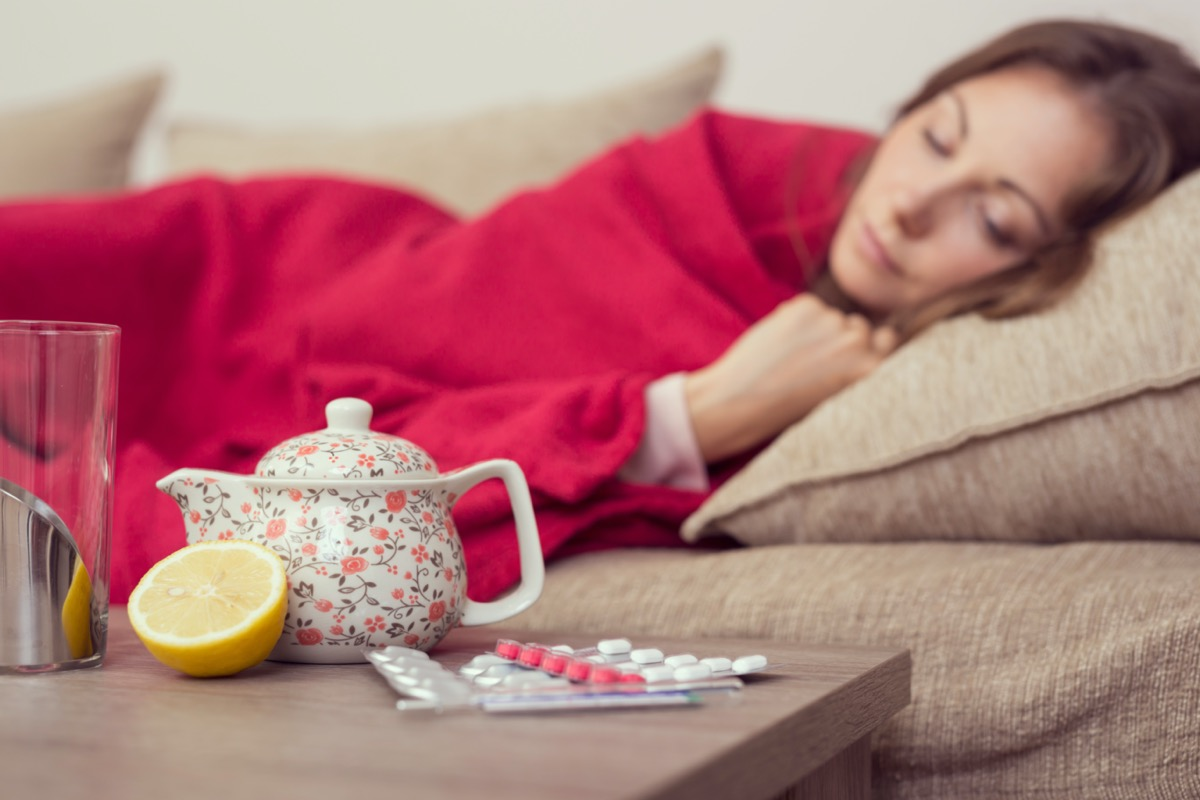 Sick woman covered with a blanket lying in bed with high fever and a flu, resting